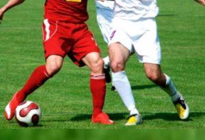 Спортсмены играют в футбол